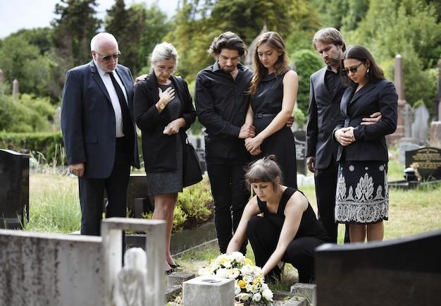 Família colocando flores no túmulo Foto Premium