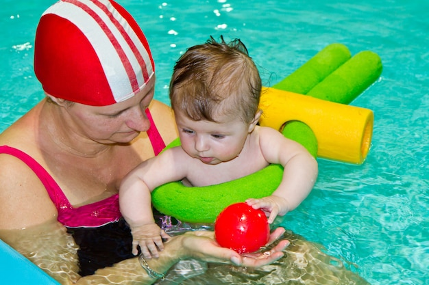 Família com bebê na piscina Foto Premium