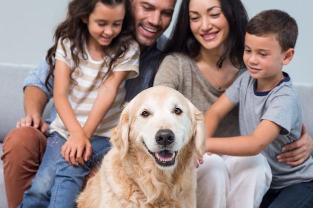 Família com cachorro na sala de estar Foto Premium