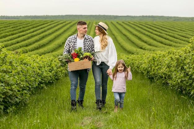 Família com cesta de legumes Foto Premium