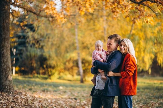 Família com filha caminhando em um parque de outono Foto gratuita