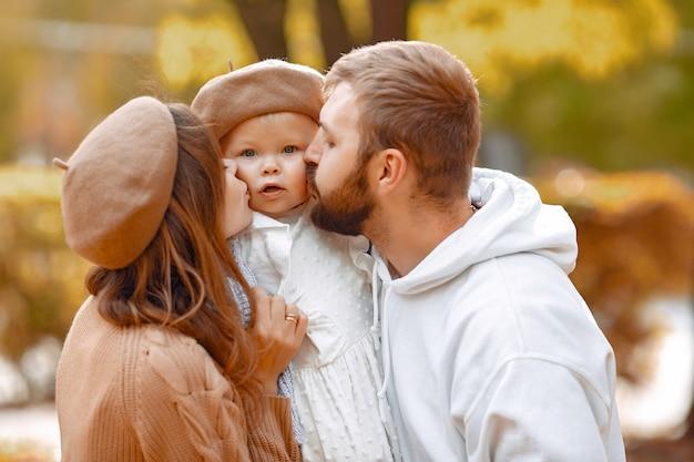 Família com filha em um parque de outono Foto gratuita