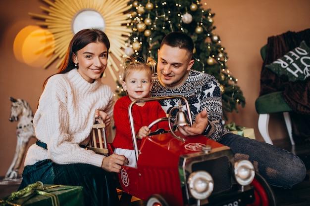 Família com filha pequena com presente de natal pela árvore de natal Foto gratuita