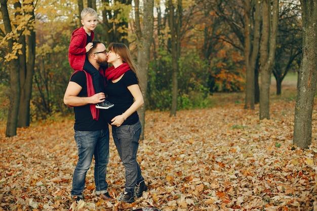 Família com filho pequeno em um parque de outono Foto gratuita