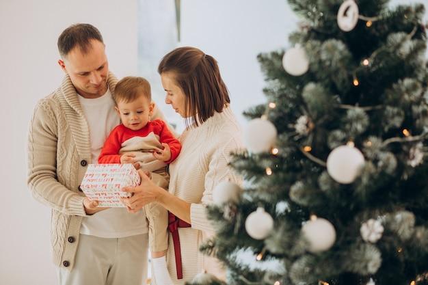 Família com filho pequeno no natal perto da árvore de natal em casa Foto gratuita