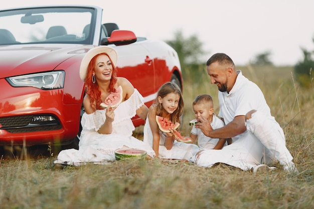 Família com melancia. pai em uma camiseta branca. pessoas em um piquenique. Foto gratuita