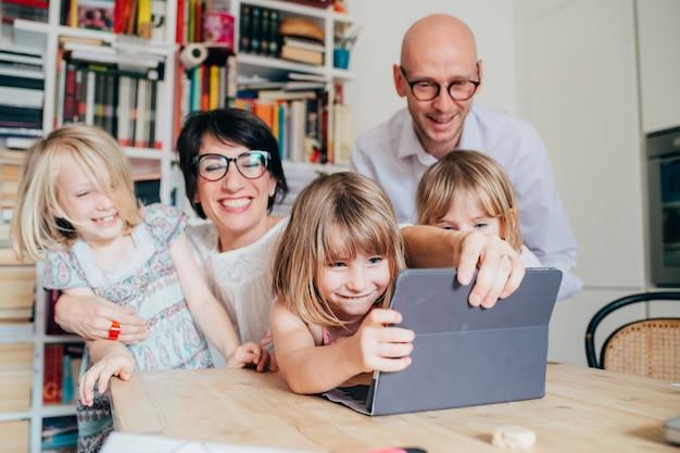 Família, com, três crianças, indoor, usando, tabuleta Foto Premium