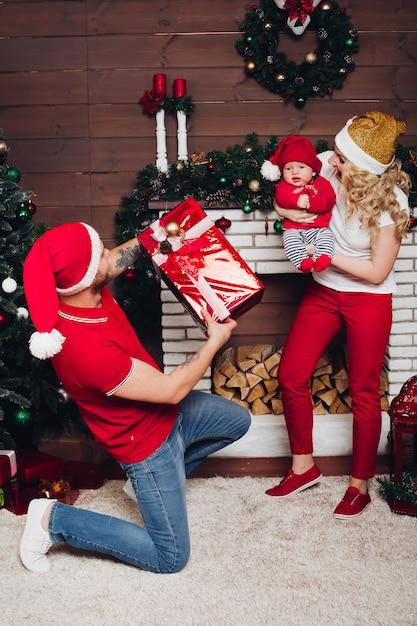 Família comemorando juntos e curtindo presentes de natal Foto Premium