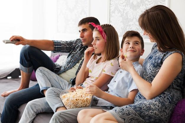 Família comendo pipoca enquanto assistia televisão em casa Foto gratuita