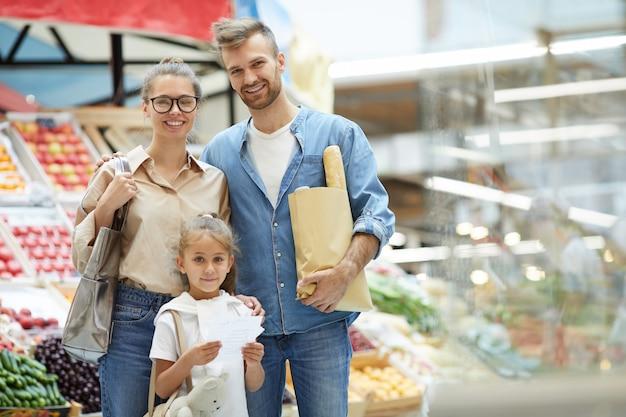 Família contemporânea posando no supermercado Foto Premium