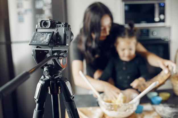 Família cozinha a massa para biscoitos enquanto está sendo gravada Foto gratuita