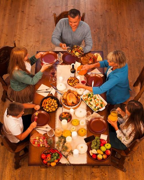 Família de alto ângulo sentada à mesa de jantar Foto gratuita
