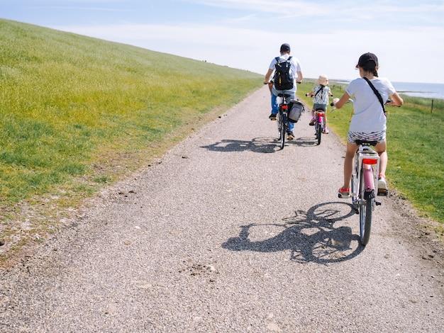 Família de ciclistas vista traseira viajando na estrada na área das dunas da ilha de schiermonnikoog. Foto Premium