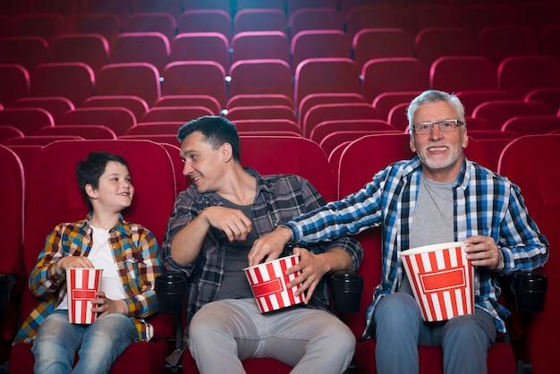 Família de diferentes gerações no cinema Foto gratuita