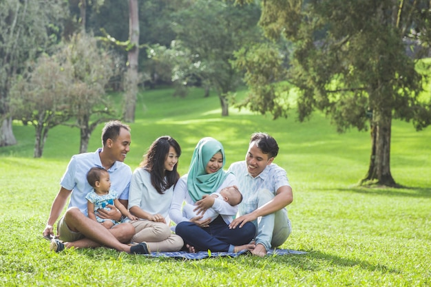 Família de dois jovens no parque, aproveitando a primavera juntos Foto Premium