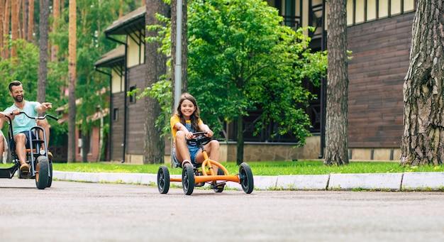 Família de jovem turista moderna e feliz de férias, andando de bicicleta e se divertindo juntos Foto Premium