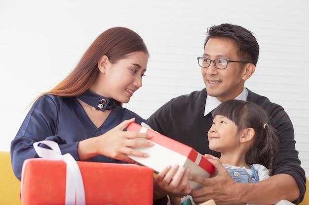 Família de natal e boas festas. mãe e pai que guardam o presente atual com as crianças na sala de visitas branca. Foto Premium