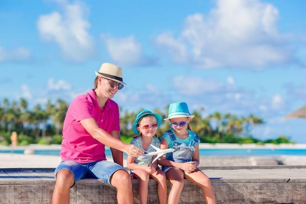 Família de pai e filhos na praia de areia branca Foto Premium