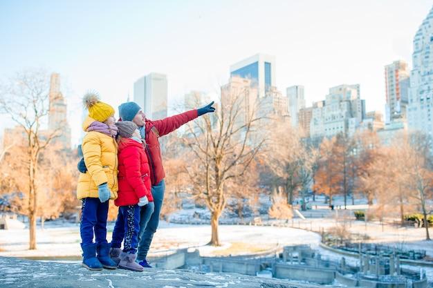 Família de pai e filhos no central park durante suas férias em nova york Foto Premium
