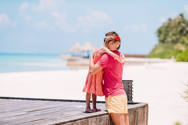 Família de pai e menina desportiva se divertindo na praia Foto Premium