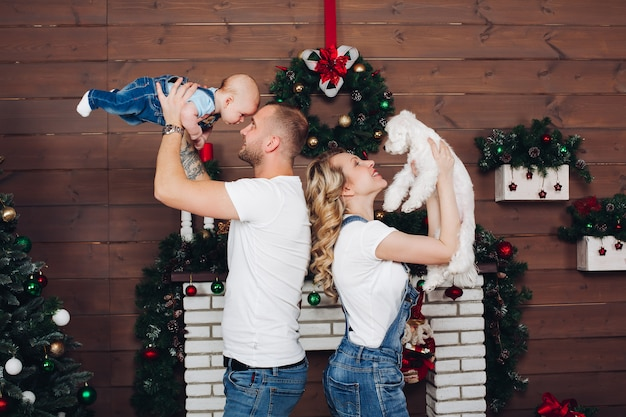 Família de positividade posando juntos perto da lareira e presentes para o natal Foto Premium