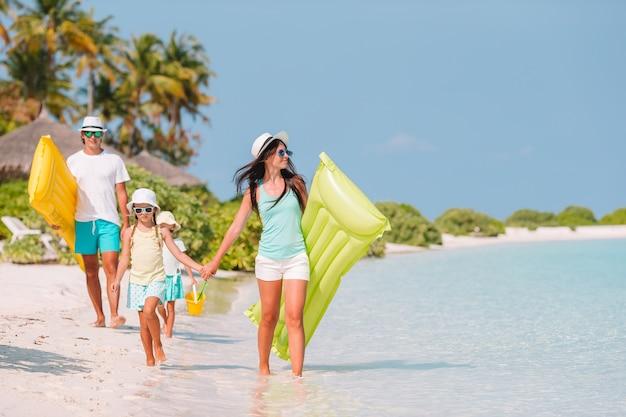 Família de quatro em férias de praia se divertir Foto Premium