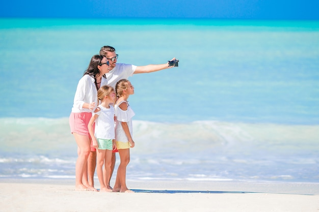 Família de quatro pessoas que toma uma foto do selfie na praia. férias em família Foto Premium