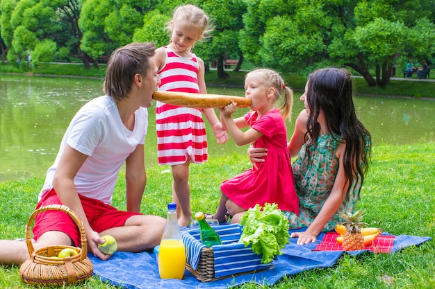 Família de quatro pessoas têm piquenique no parque no dia de verão Foto Premium