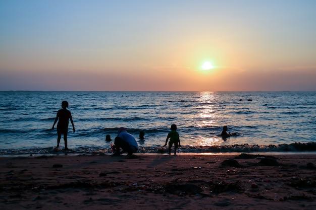 Família de silhueta e animal de estimação na praia e mar areia pôr do sol Foto Premium