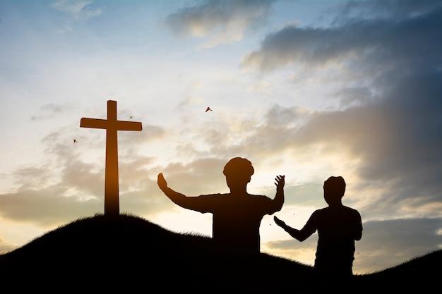 Família de silhueta procurando a cruz de jesus cristo no nascer do sol de outono Foto Premium