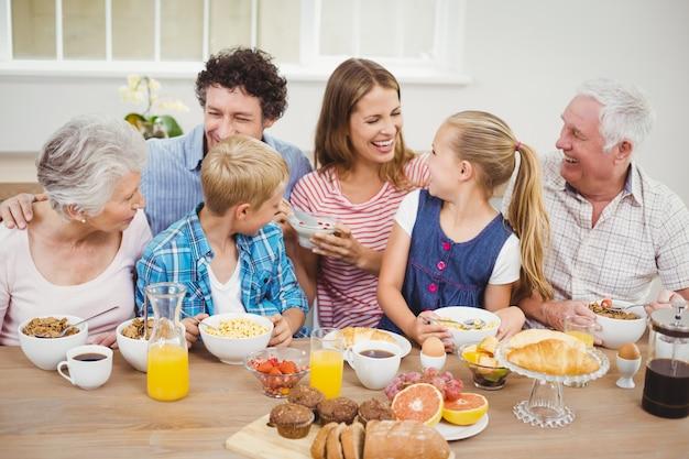Família de várias gerações alegre tomando café da manhã Foto Premium