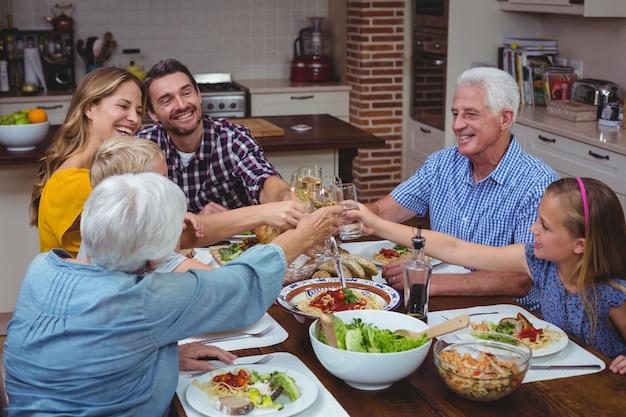 Família de várias gerações, brindando vinho branco enquanto comemorava o dia de ação de graças Foto Premium