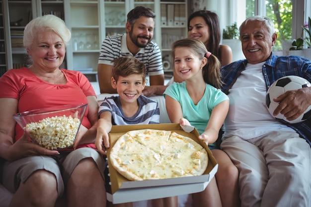 Família de várias gerações, sentada com pipoca e pizza, enquanto assiste a partida de futebol Foto Premium