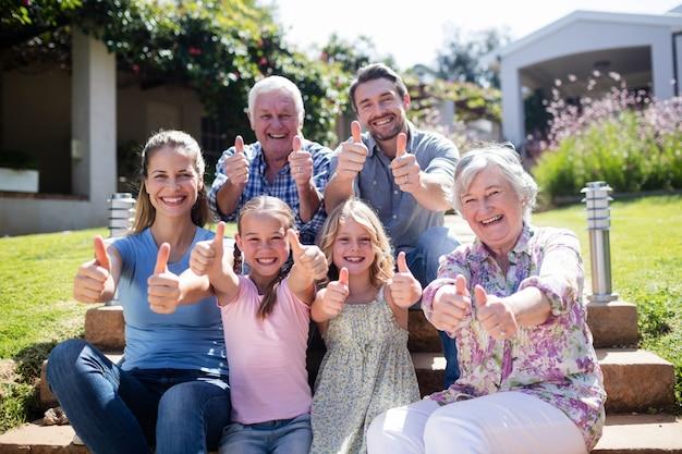 Família de várias gerações, sentada no jardim Foto Premium