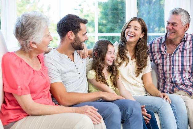 Família de várias gerações, sorrindo enquanto está sentado no sofá Foto Premium