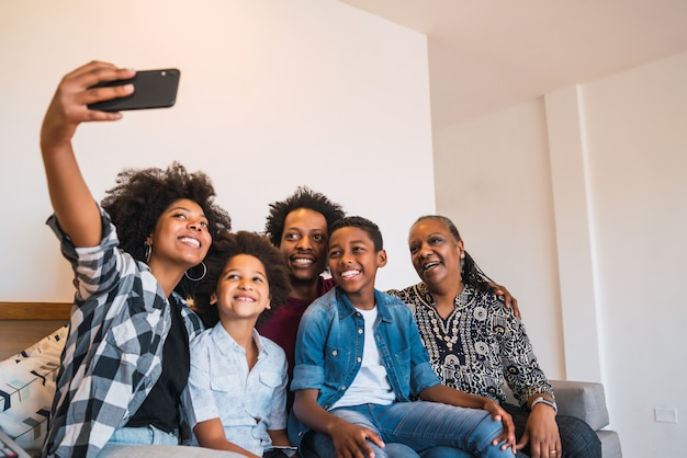 Família de várias gerações, tendo selfie com telefone em casa. Foto gratuita