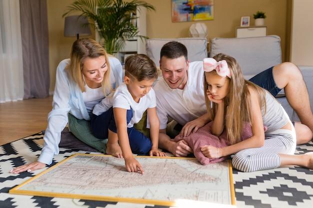 Família de vista frontal dentro de casa, olhando para uma impressão azul Foto gratuita