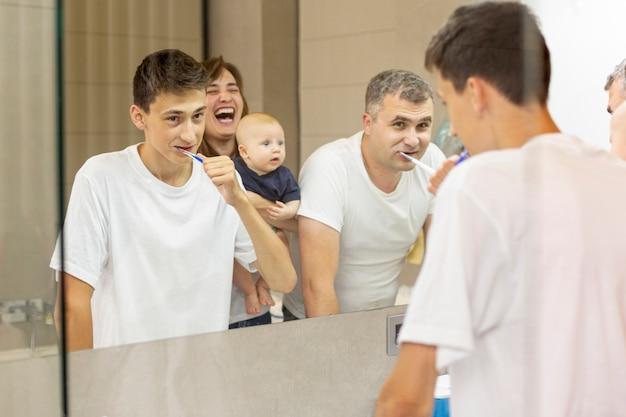 Família de vista lateral olhando no espelho Foto gratuita