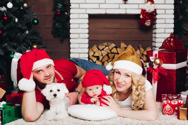 Família, deitado no chão perto da lareira com filho e cachorro e sorrindo para a câmera Foto Premium