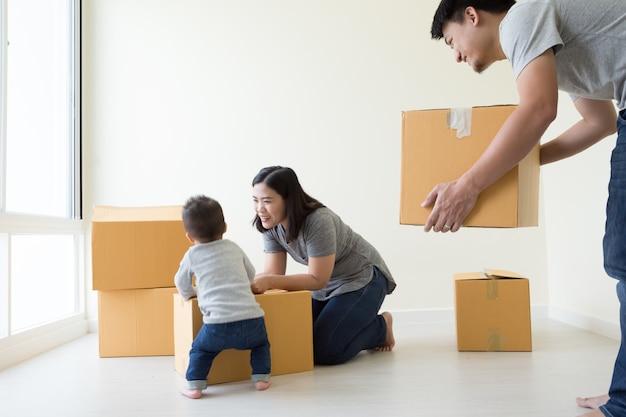 Família desembalar caixas na nova casa no dia da mudança Foto Premium