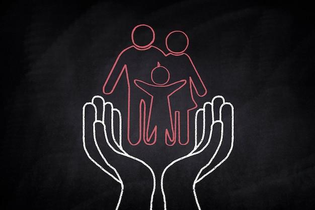 Família desenhado em um quadro negro em algumas mãos Foto gratuita