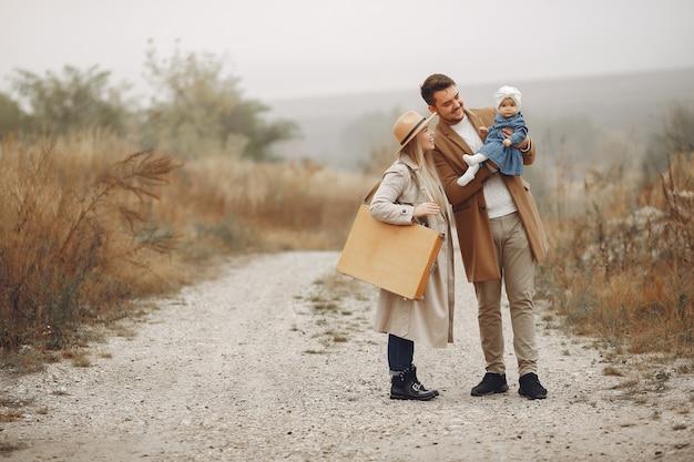 Família elegante andando em um campo de outono Foto gratuita
