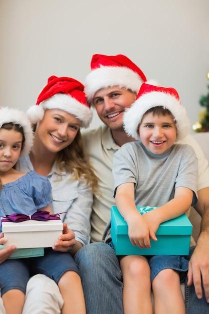 Família, em, chapéu natal, segurando apresenta, ligado, sofá Foto Premium