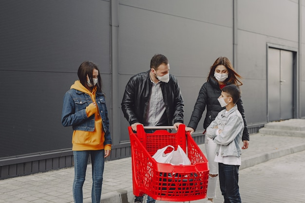 Família em máscaras protetoras com compras Foto gratuita