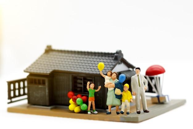 Família em miniatura na frente da casa Foto Premium