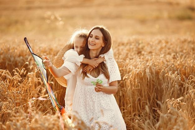 Família em um campo de trigo. mulher de vestido branco. criança com pipa. Foto gratuita