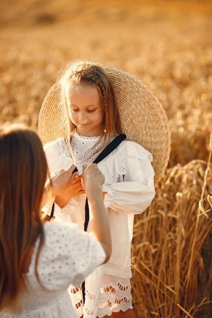 Família em um campo de trigo. mulher de vestido branco. menina com chapéu de palha. Foto gratuita