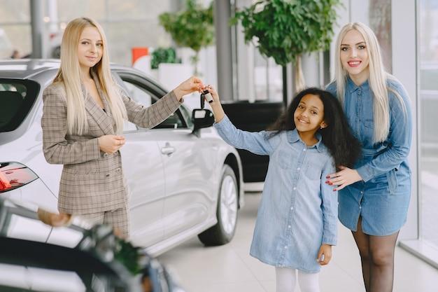 Família em um salão de automóveis. mulher comprando o carro. menina africana com mther. gerente com clientes. Foto gratuita