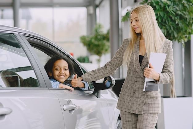 Família em um salão de automóveis. mulher comprando o carro. menina africana com mther. Foto gratuita