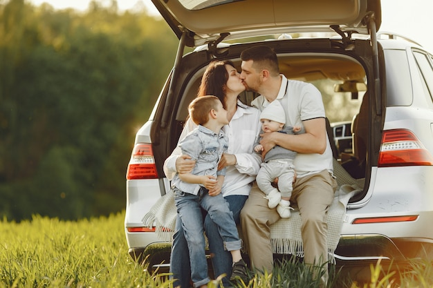 Família em uma floresta de verão pelo porta-malas aberto Foto gratuita